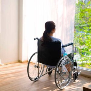 girl sitting in wheelchair staring out of the window